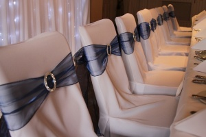 Chair Covers dressed with beautiful Midnight Blue organza sashes and accessorised with stunning Diamanté Buckles.