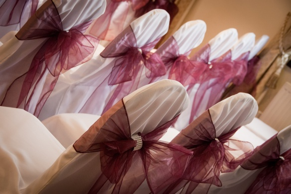 Chair Covers dressed with burgundy organza sashes.